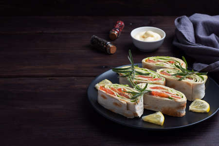 Rolls of thin pita bread and red salted salmon with lettuce leaves on a black ceramic plate, dark wooden background. Copy space