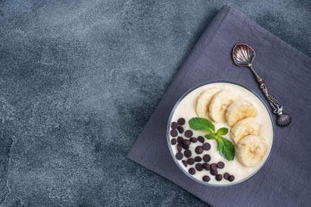 Healthy breakfast, dessert with milk yogurt banana and chocolate on a plate. Dark concrete background. Top view, copy space 免版税图像