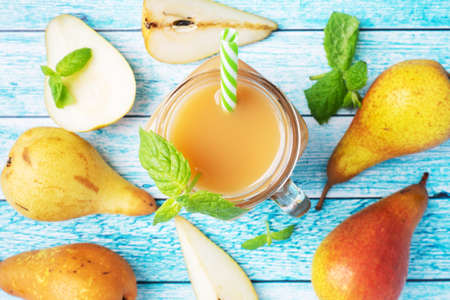 Natural pear juice in a glass cup. Juicy ripe conferences pears and mint leaves top view Bright blue background. 免版税图像