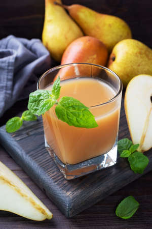 Natural pear juice in a glass cup. Juicy ripe conferences pears and mint leaves Dark rustic wooden background. 免版税图像