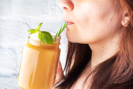 A young girl holds a glass mug with juice in her hand and drink. Fresh juice with mint. Selective focus