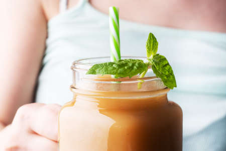 A young girl holds a glass mug with juice in her hand. Fresh juice with mint. Selective focus