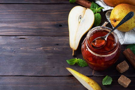 Homemade pear jam in a jar and fresh pears on a wooden background copy space 免版税图像
