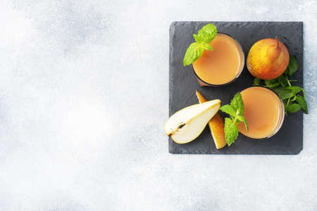 Natural pear juice in a glass cup. Juicy ripe conferences pears and mint leaves top view copy space Slate stand, light concrete background.