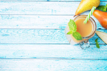 Natural pear juice in a glass cup. Juicy ripe conferences pears and mint leaves top view copy space Bright blue background. 免版税图像