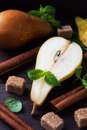 Ripe juicy yellow pears with cinnamon on wooden background. Conference pears for caramelization