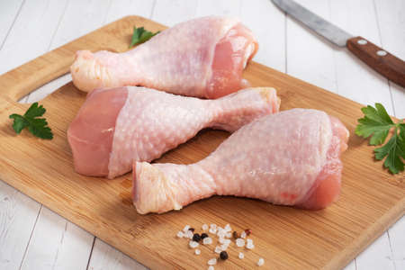 Raw chicken drumsticks with parsley and spices on a wooden cutting Board 免版税图像