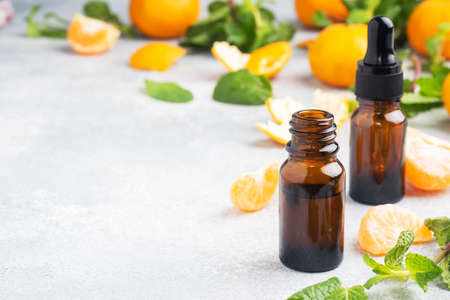 Aromatic tangerine oil in a dark bubble, cosmetic oil from Mandarin on a light gray background, copy space 免版税图像