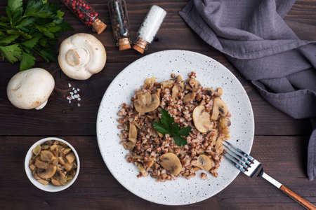 Boiled buckwheat with stewed mushrooms. Russian traditional food. Healthy diet food copy space, top view.