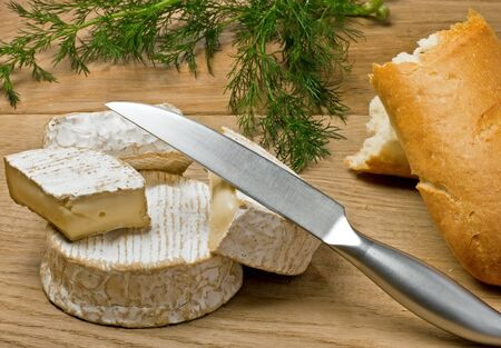Brie, Camembert, bread and dill on the wood surface, outdoor photo