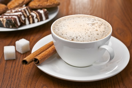 Cappuccino with cinnamon bark, lump sugar and plate of sweets on the table photo