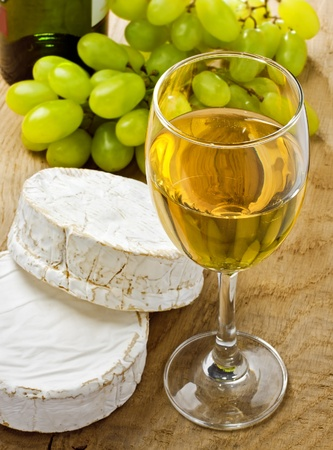 White wine, brie, caembert and grape on the wood surface