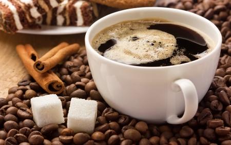 cafe y pastel: Taza de caf�, la canela y cubos de az�car en granos de caf�, los dulces en el fondo Foto de archivo