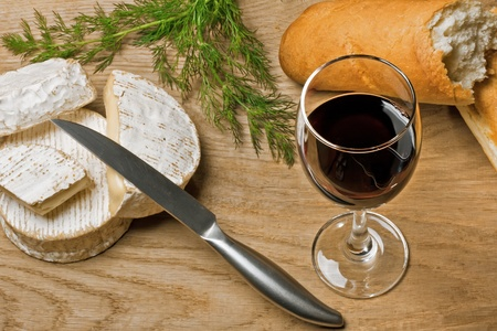 Red wine, Brie and Camembert cheeses with bread on the wood surface, studio shot photo