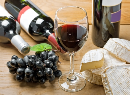 Red wine, Brie, Camembert and grape on the wood surface, studio shot photo