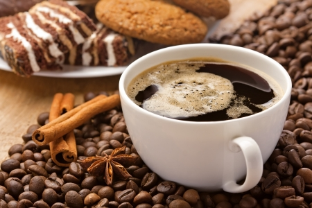 coffee shop: Coffee cup, cinnamon, anise on coffee beans, sweets on the background Stock Photo