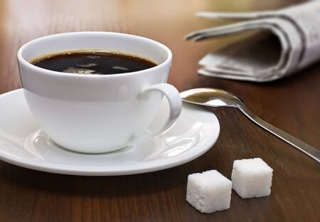 Coffee cup, lump sugar (sugar cubes) and newspapers on a table
