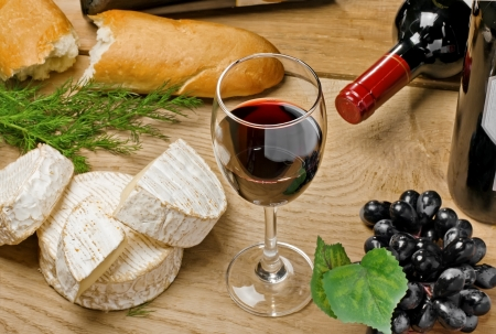 Red wine, Brie and Camembert cheeses with bread on the wood surface, studio shot Stock Photo