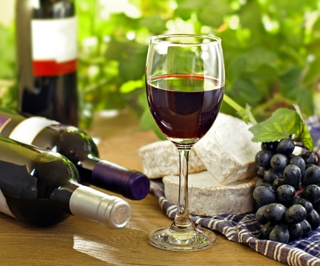 french cuisine: Red wine, Brie, Camembert and grape on the wood surface, outdoor