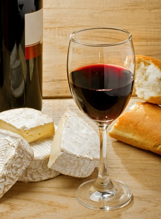 Red wine, Brie, Camembert and bread on the wood surface, studio shot photo