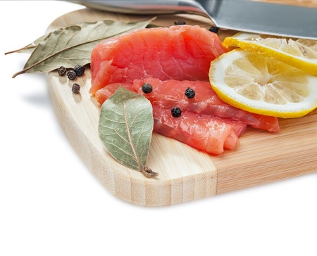 Salmon slices on the wooden board, isolated on white, studio shot photo
