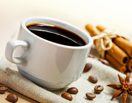 non alcoholic beverage: Coffee cup, beans, cinnamon and anise on a table