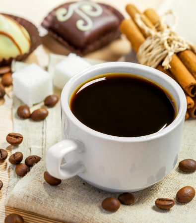 non alcoholic beverage: Coffee cup, beans, chocolate candy, cinnamon, sugar and anise on a table Stock Photo