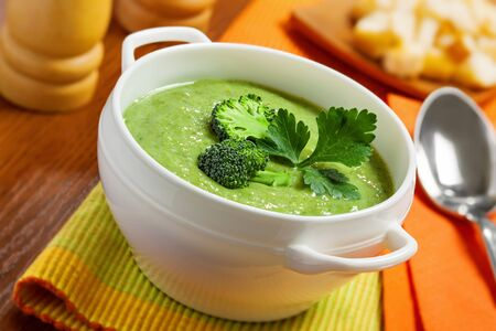 Broccoli cream soup on table photo
