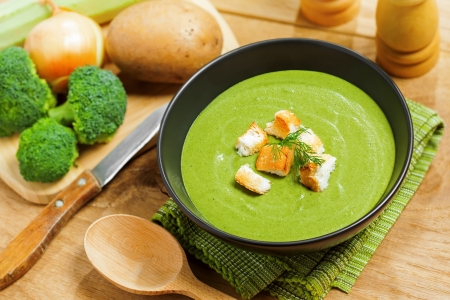 Broccoli cream soup and ingredients on table Stock Photo