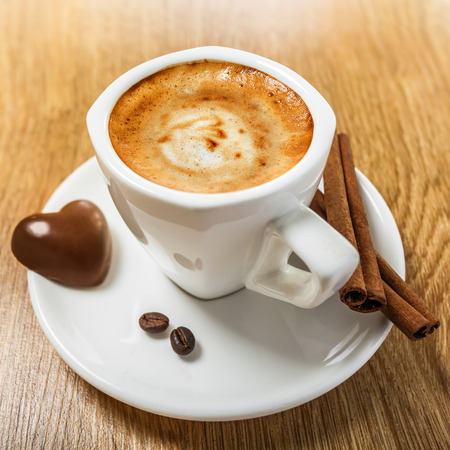 Coffee with candy heart and cinnamon photo
