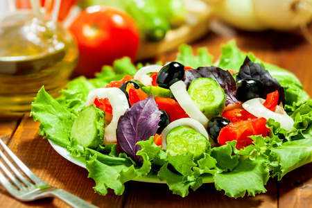 Delicious vegetable salad on table with ingredients