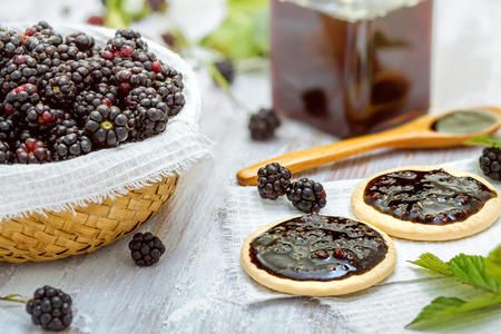 jam sandwich: Fresh blackberries with jam sandwich biscuits on table Stock Photo