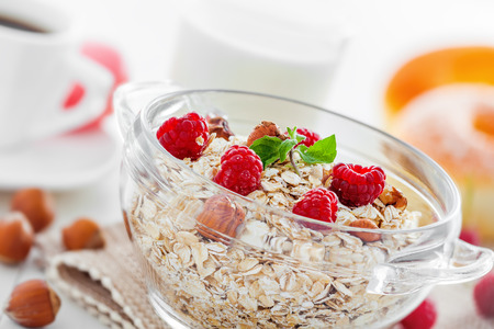 oatmeal bowl: Delicious healthy food breakfast. Oatmeal  muesli with raspberry and hazelnut on table.