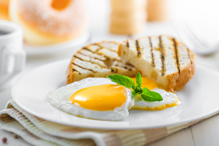 Fried eggs with toasts, coffee and donuts, traditional breakfast, close-up Stock Photo
