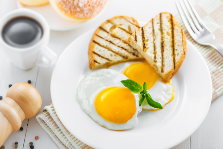 Healthy breakfast on table. Fried eggs with coffee and donuts. Stock Photo