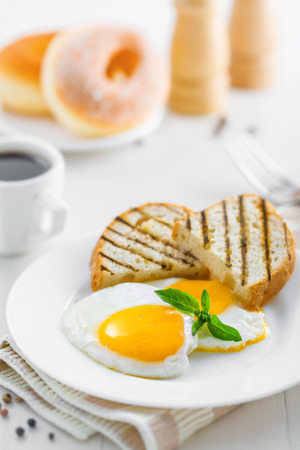 Healthy breakfast on table. Fried eggs with coffee and donuts. Stock Photo - 47214145