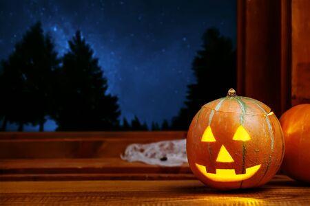Halloween Jack O Lantern pumpkin indoor, night sky full of stars outside