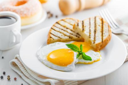Ontbijt met gebakken eieren, koffie en dessert op tafel. Gezond eten