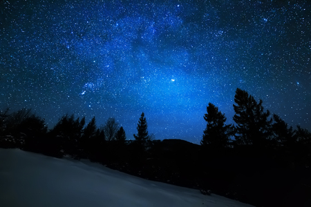 Milky Way in sky full of stars. Winter mountain landscape in night. Stock Photo