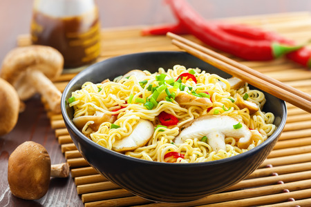 Makaron instant z grzybami shiitake, papryką i cebulą w misce, azjatyckie jedzenie na stole
