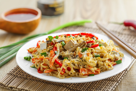 stirred: Stirred rice noodles with vegetables, tofu and shiitake mushroom. Traditional Asian food. Stock Photo