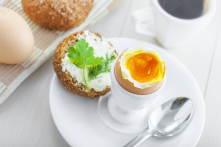 Perfect soft boiled egg, bread and butter with coffee for breakfast. Traditional healthy food. Top view.