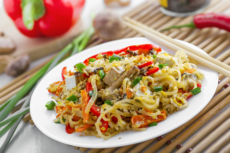 oriental cuisine: Asian meal made of rice noodles, tofu, vegetables and shiitake mushrooms. Traditional Oriental cuisine meal.