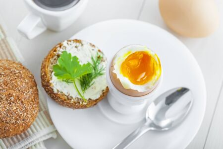 Healthy breakfast with perfect soft boiled egg, bread and butter, coffee cup. Delicious homemade food.