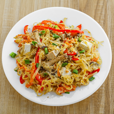 stirred: Plate of stirred rice noodles with tofu, vegetables and shiitake on a table. Traditional Asian cuisine meal. Top view. Stock Photo