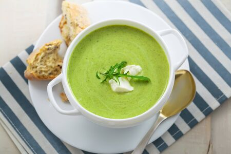 Delicious spinach cream soup with rye bread on a table. International meal. Top view.