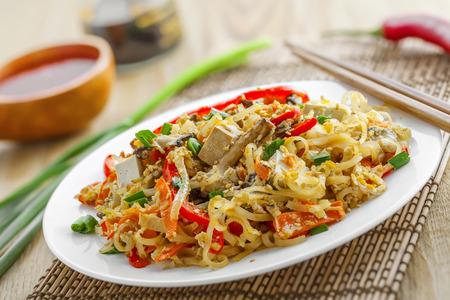 oriental cuisine: Asian food. Fried rice noodles with tofu, vegetables and shiitake mushroom. Oriental cuisine meal.