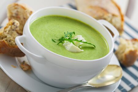 european food: Spinach cream soup with rye bread on a table. Traditional European food for lunch.