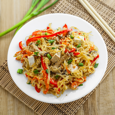 oriental cuisine: Asian meal made of rice noodles, tofu, vegetables and shiitake mushrooms. Traditional Oriental cuisine meal. Top view. Stock Photo
