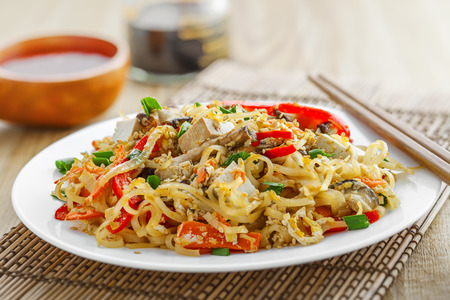 oriental cuisine: Oriental food made of rice noodles, tofu, vegetables and shiitake mushrooms. Delicious Oriental cuisine meal. Close-up.